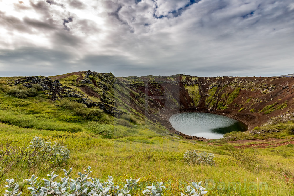 """""""Famous volcanic crater turquoise water natural lake in Iceland with some green plants in the front"""" stock image"""