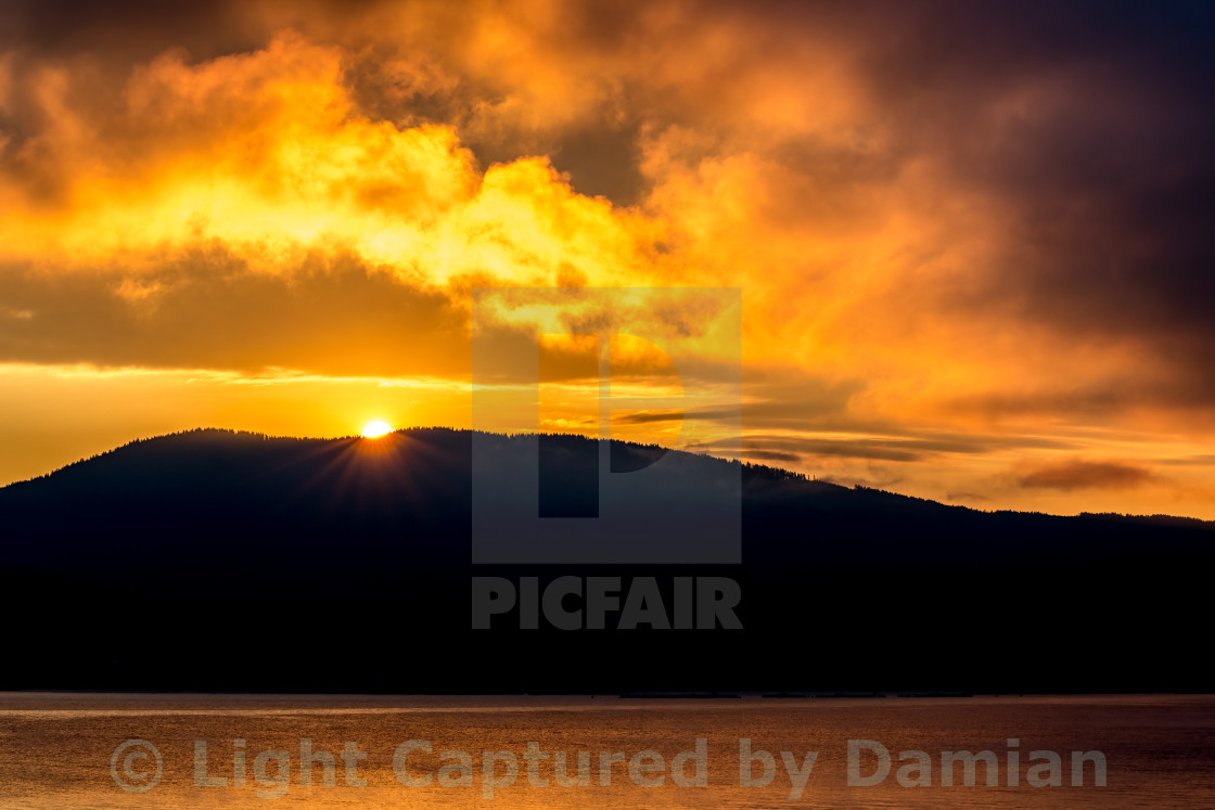 """""""The Sun is showing behind the mountain peak"""" stock image"""