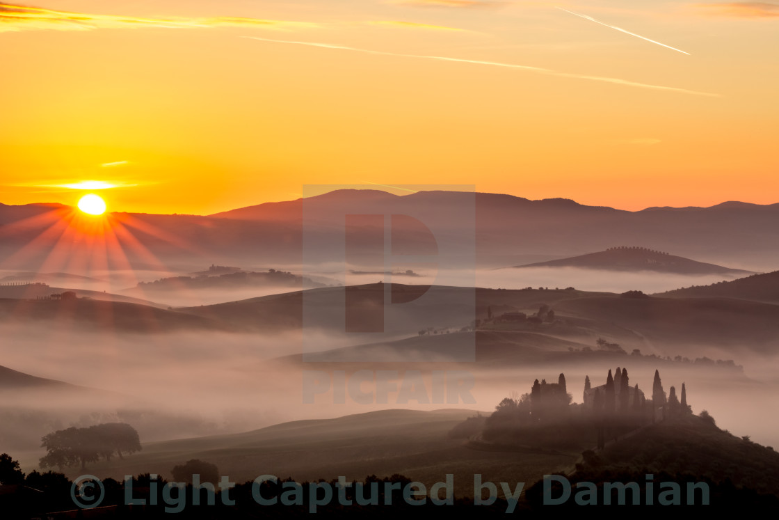 """Fog, mist and the sunrise near San Quirico d'Orcia, Tuscany, Italy"" stock image"