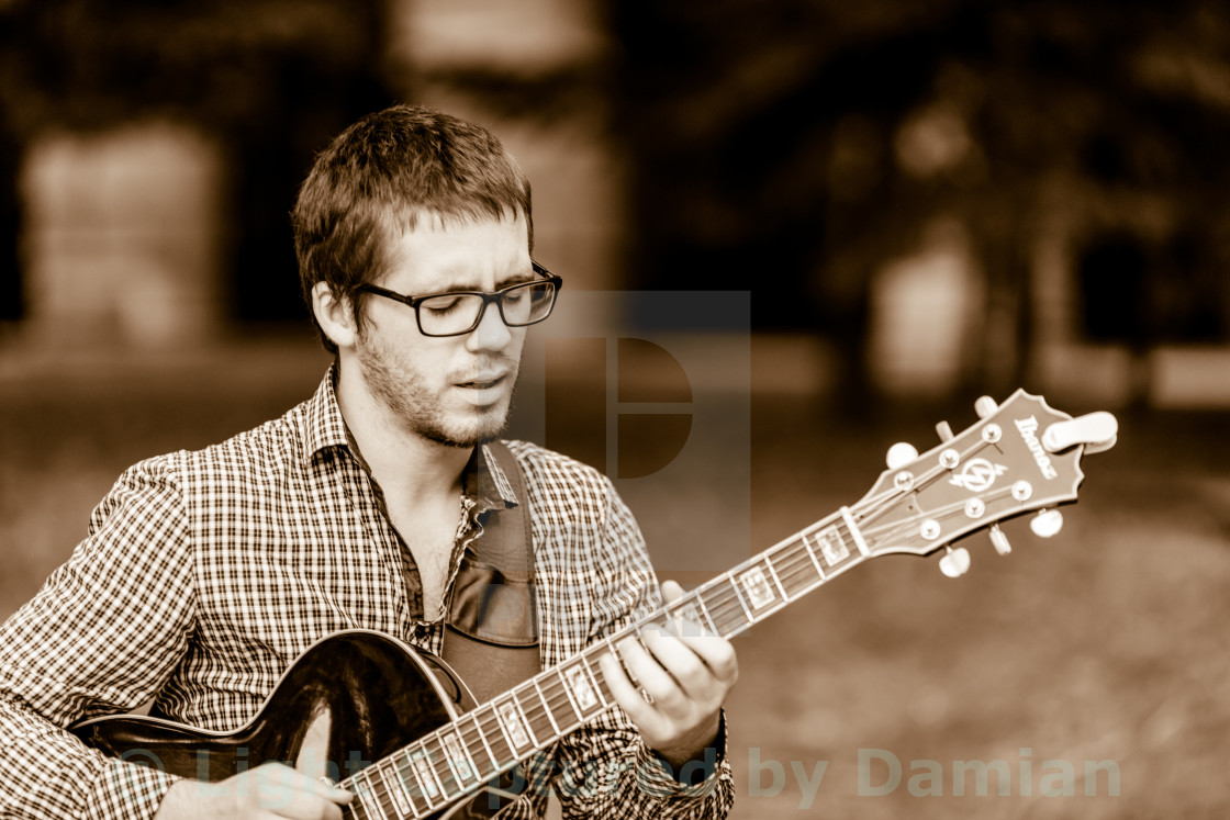 """Man playing passionately solo on a jazzy guitar"" stock image"