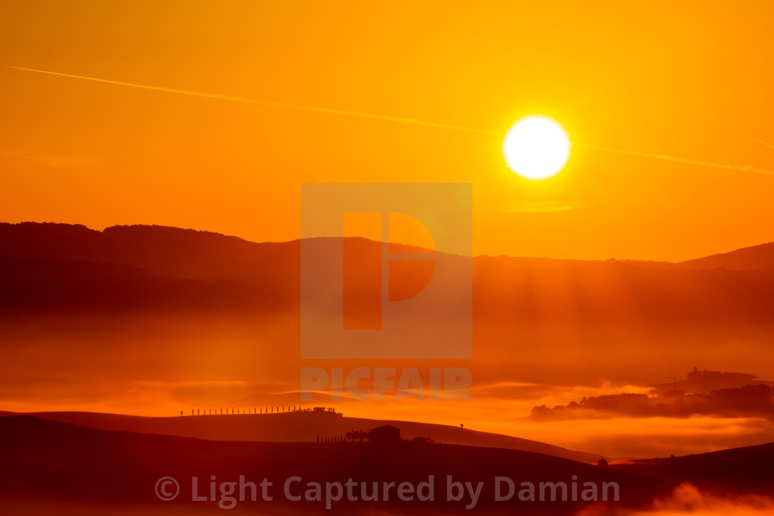 """Golden sunrise over the misty fields in Tuscany, Italy"" stock image"