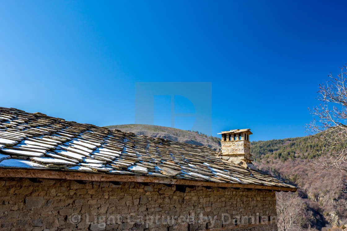 """""""Stone roof, blue sky, snow and chimney"""" stock image"""