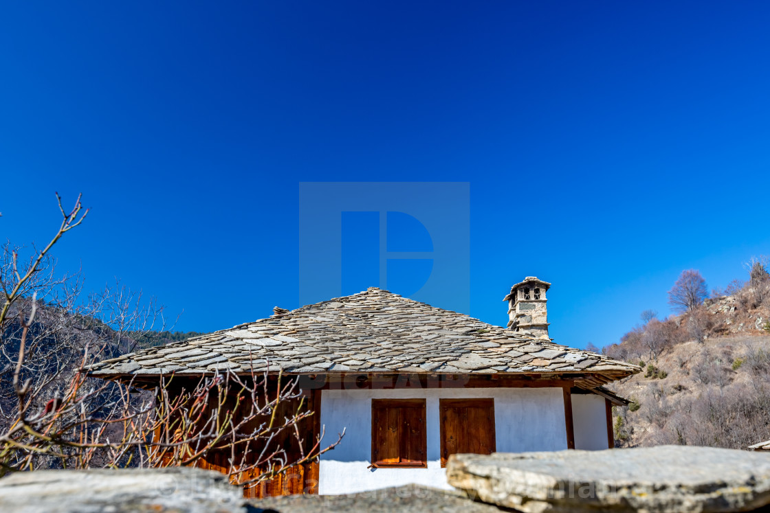 """""""Old Bulgarian house with stone roof and chimney and blue sky above"""" stock image"""