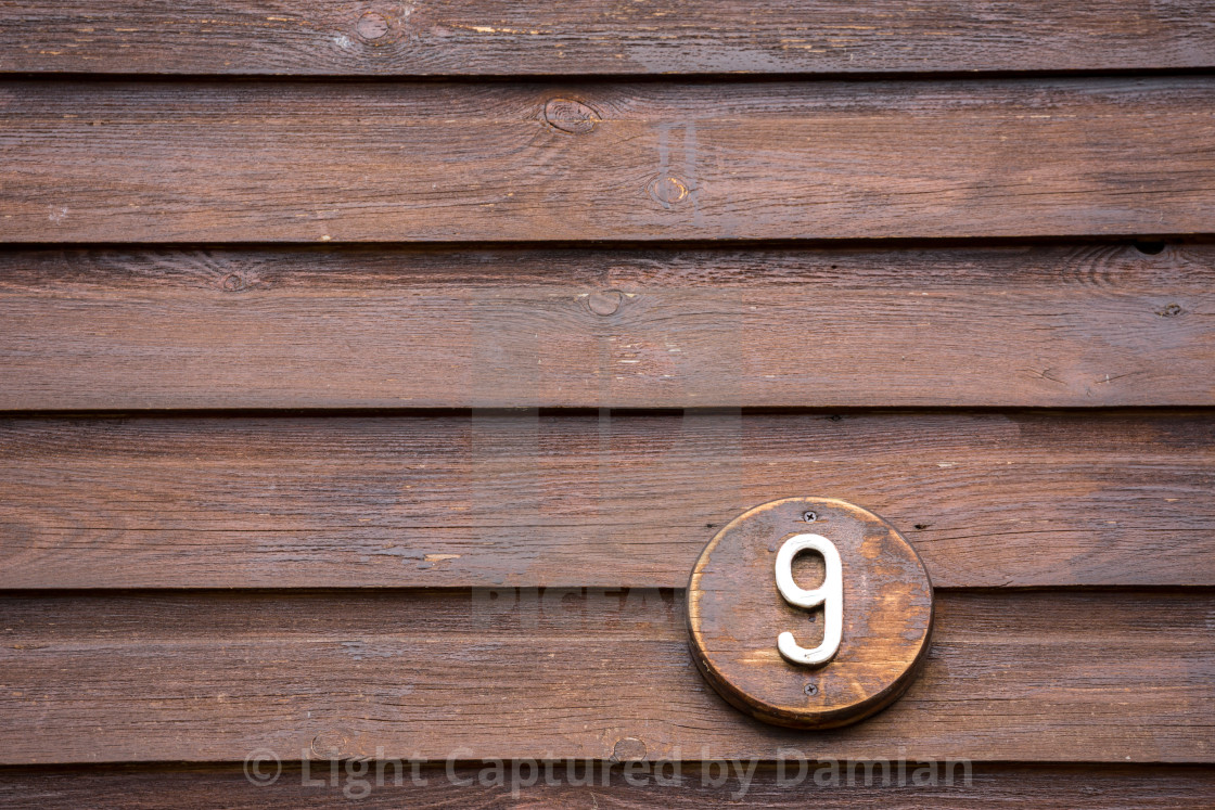 """Road sign on a house reading the number nine made out of wood"" stock image"