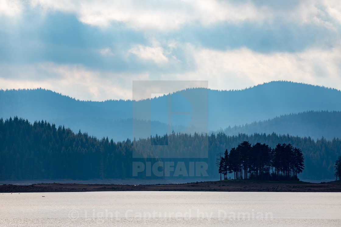 """Small island with layered mountain background"" stock image"