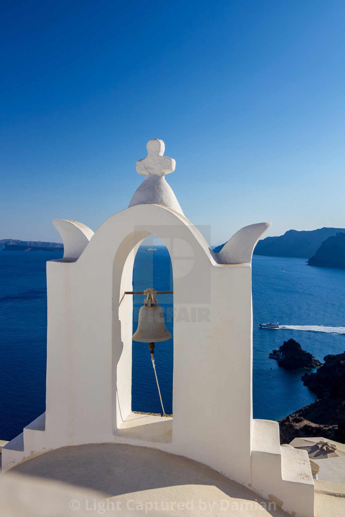 """Church white cross and bell in Santorini, Greece"" stock image"
