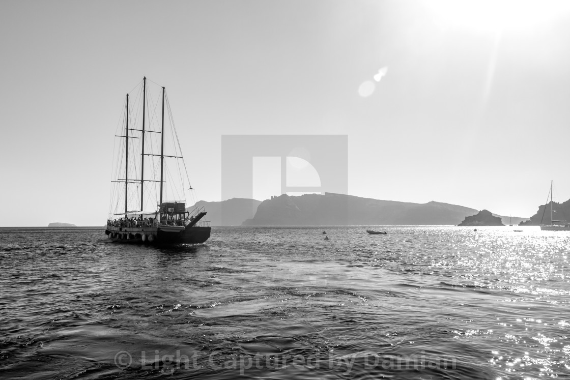 """Tourist boat sailing away in Santorini, Greece"" stock image"