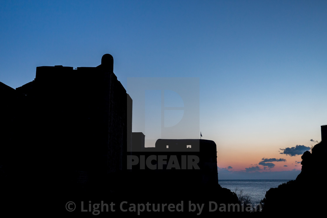 """Silhouette of Dubrovnik castle tower on sunset"" stock image"