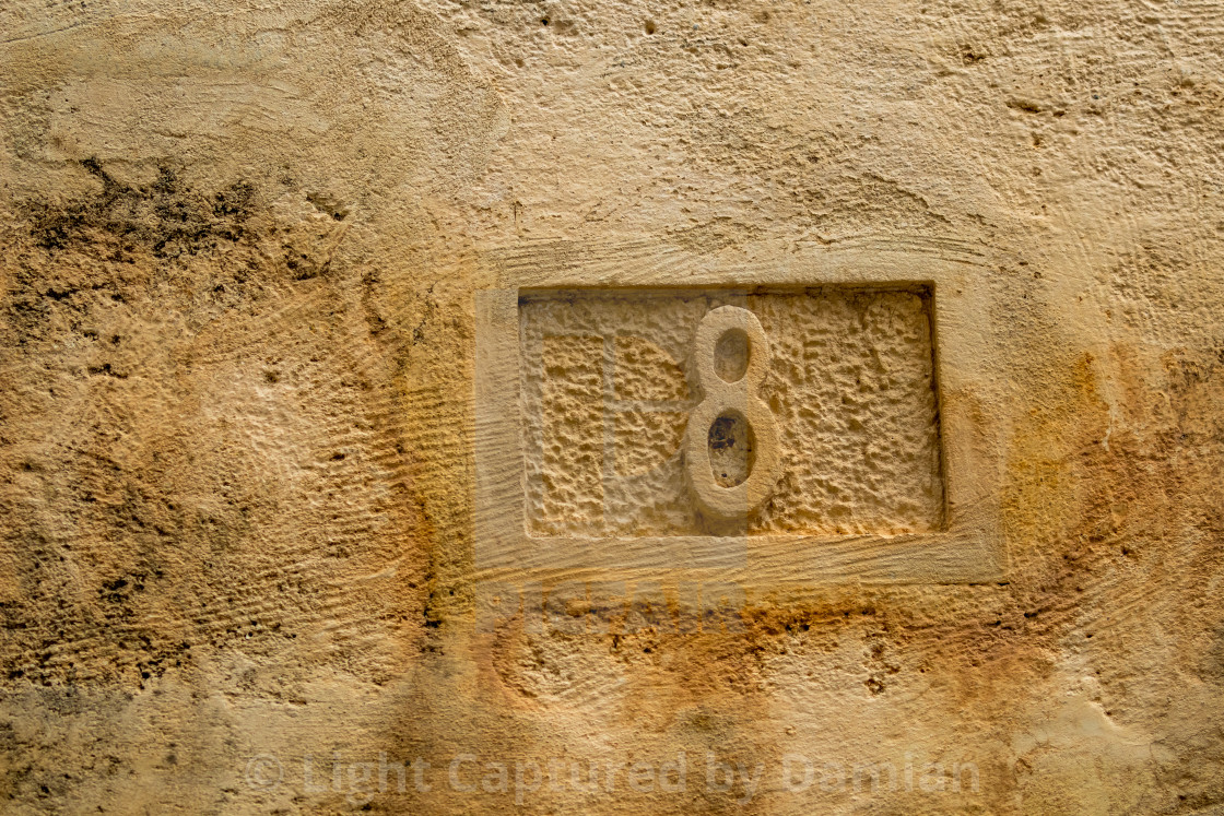 """Number eight, 8, carved in yellow limestone"" stock image"