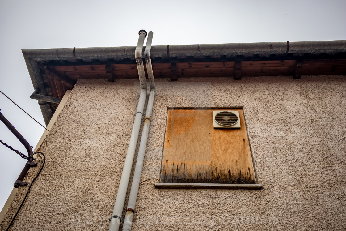 """Chipboard wood covered window on old building"" stock image"