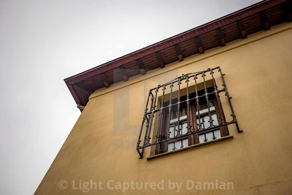 """""""Wrought iron covered window on house building"""" stock image"""
