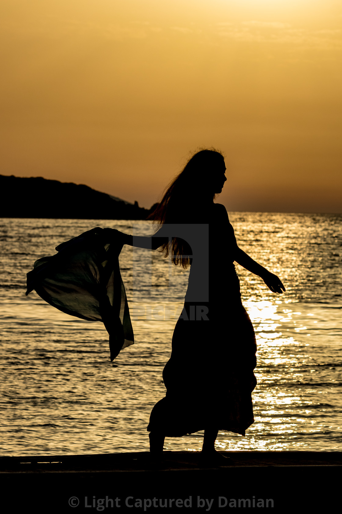 """Beautiful silhouette at sunset golden sea water"" stock image"