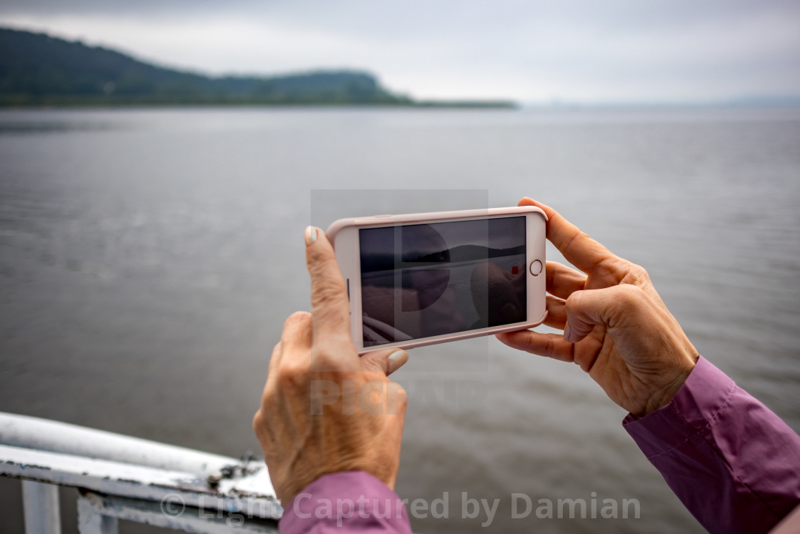 """Woman hands holding phone shooting video of lake"" stock image"