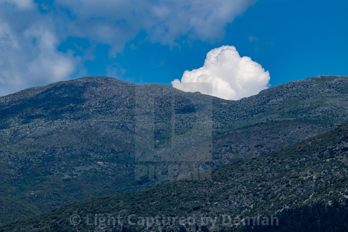 """White puffy cloud pops out from behind mountain"" stock image"