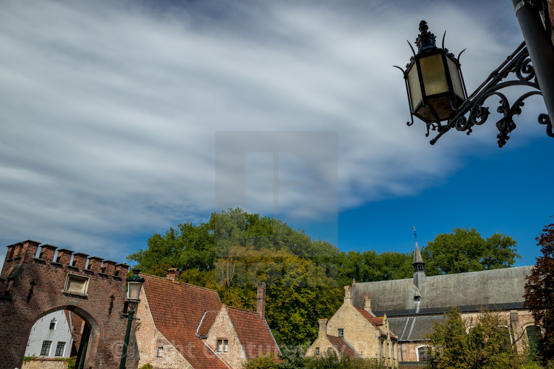 """Belgian roofs and street lamp, dynamic clouds"" stock image"