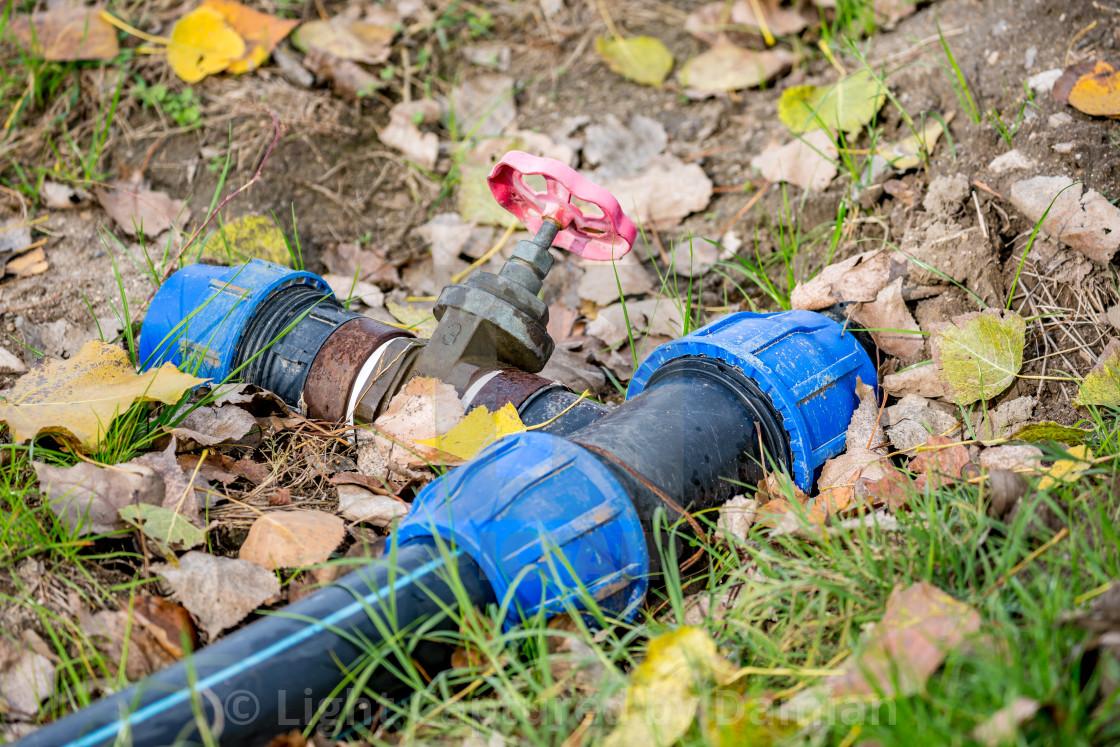 """Irrigation equipment, autumn ground with foliage"" stock image"