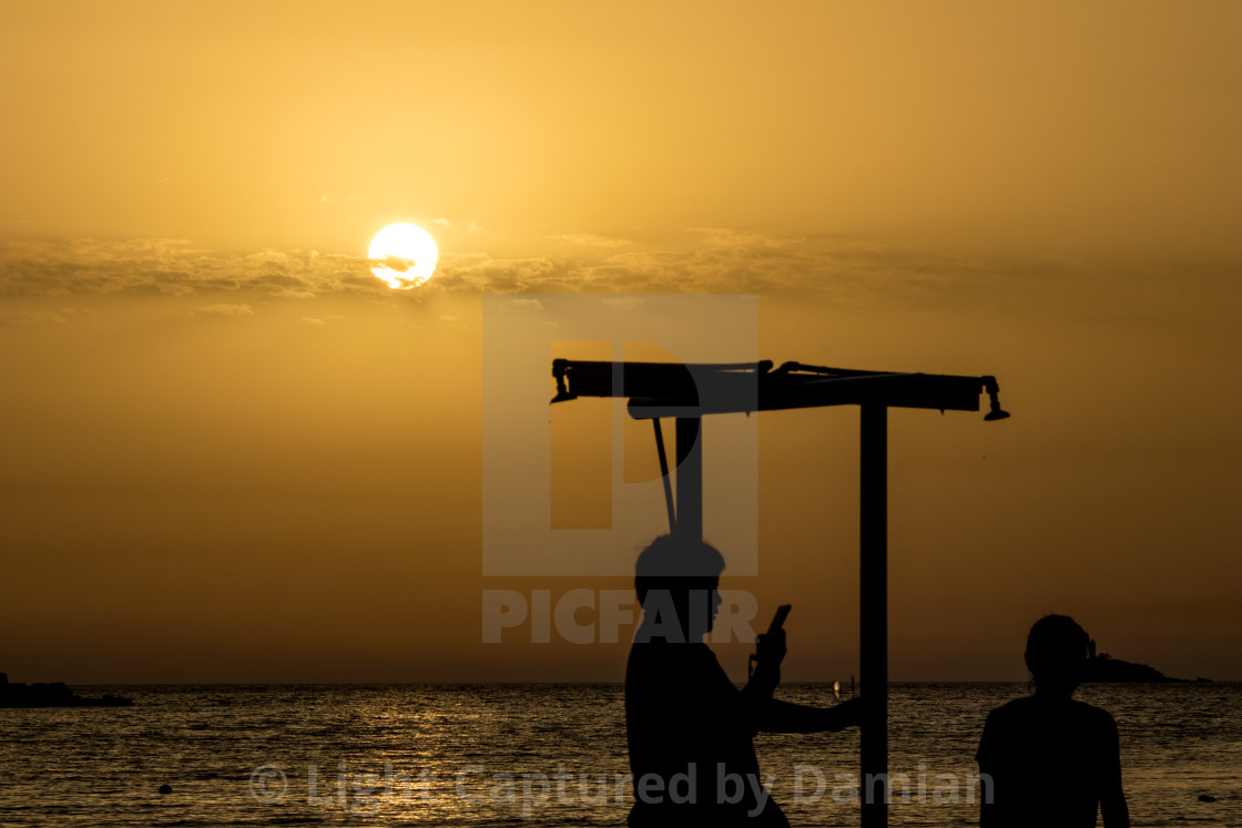 """Beautiful silhouettes at sunset golden sea water"" stock image"