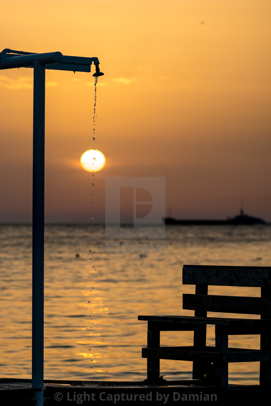"""Blurred showers silhouette at sunset golden water"" stock image"