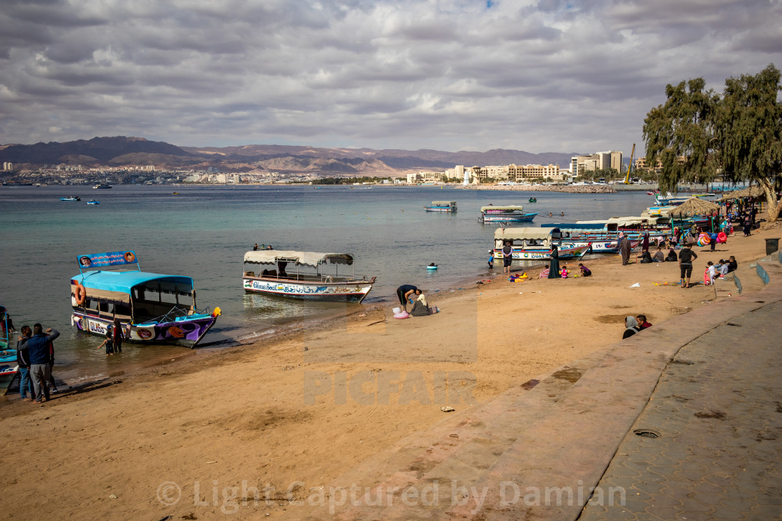 """Jordan, Aqaba, people enjoy holiday at city beach"" stock image"