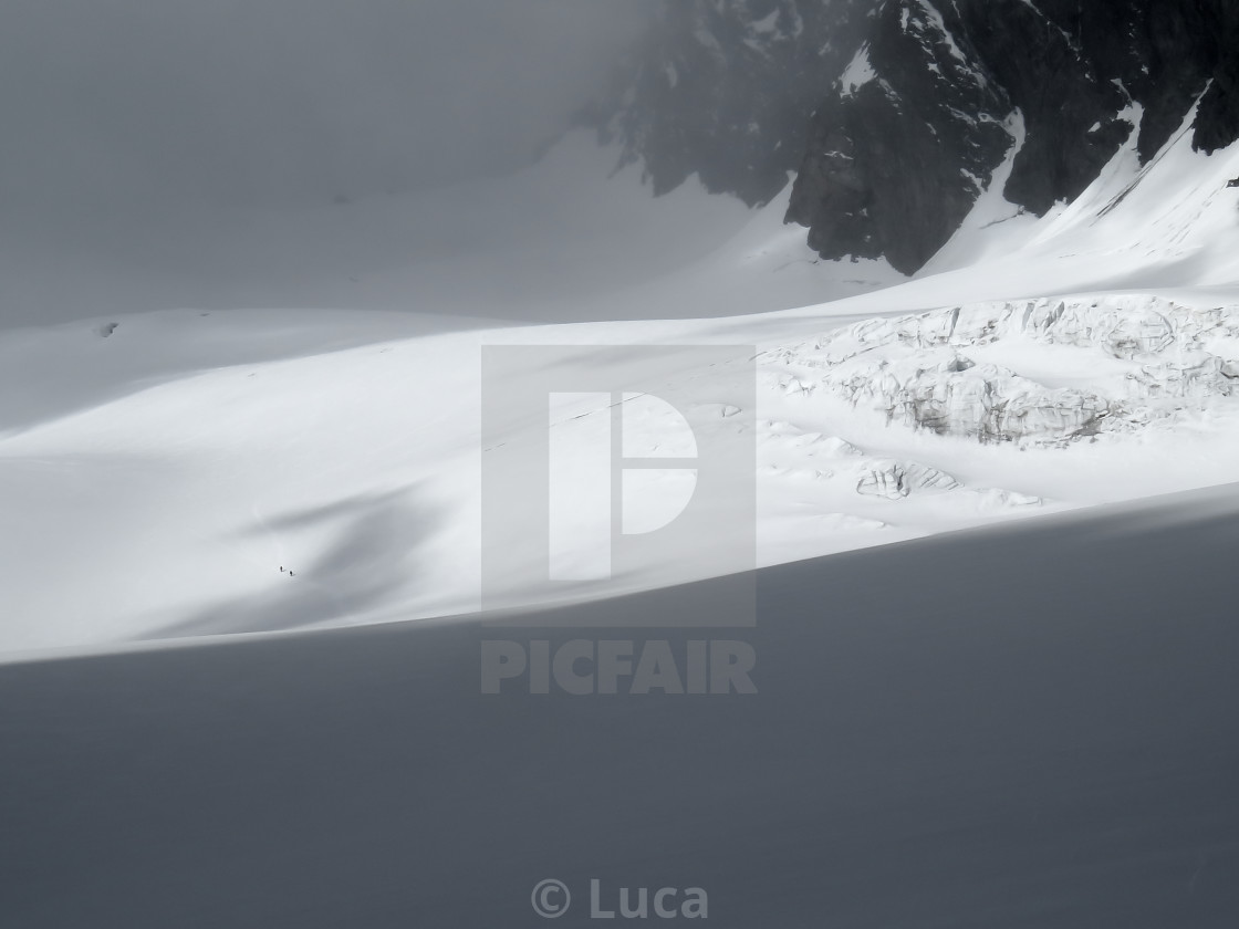 """Two men descending a glacier"" stock image"