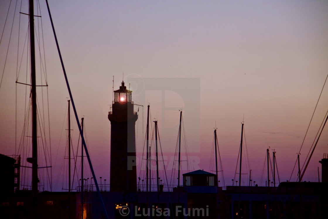 """Light house and harbor at twIlight"" stock image"