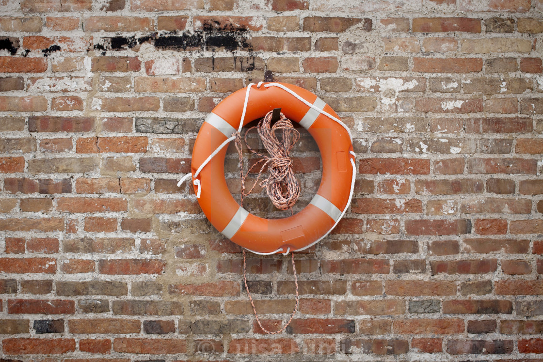 """Lifebelt for safety on sea on grunge brick wall"" stock image"