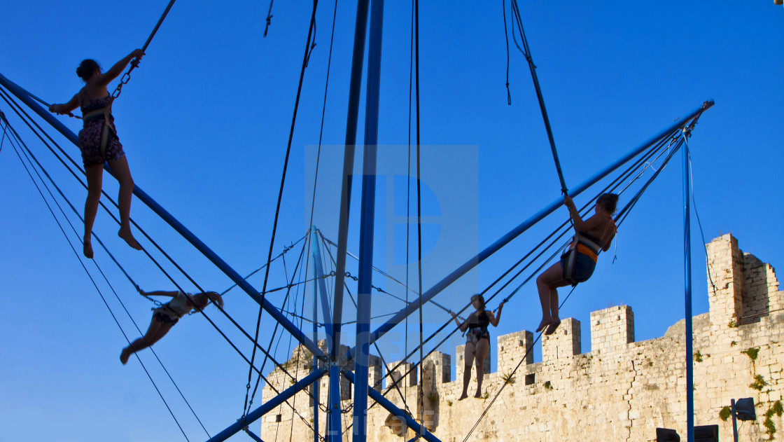 """Girls play bungee jumping near medieval castle in Trogir"" stock image"
