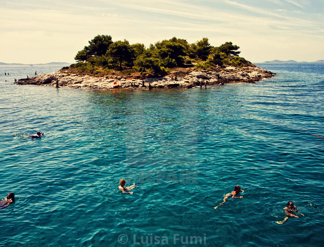 """Croatia,tourists swim near a small island"" stock image"