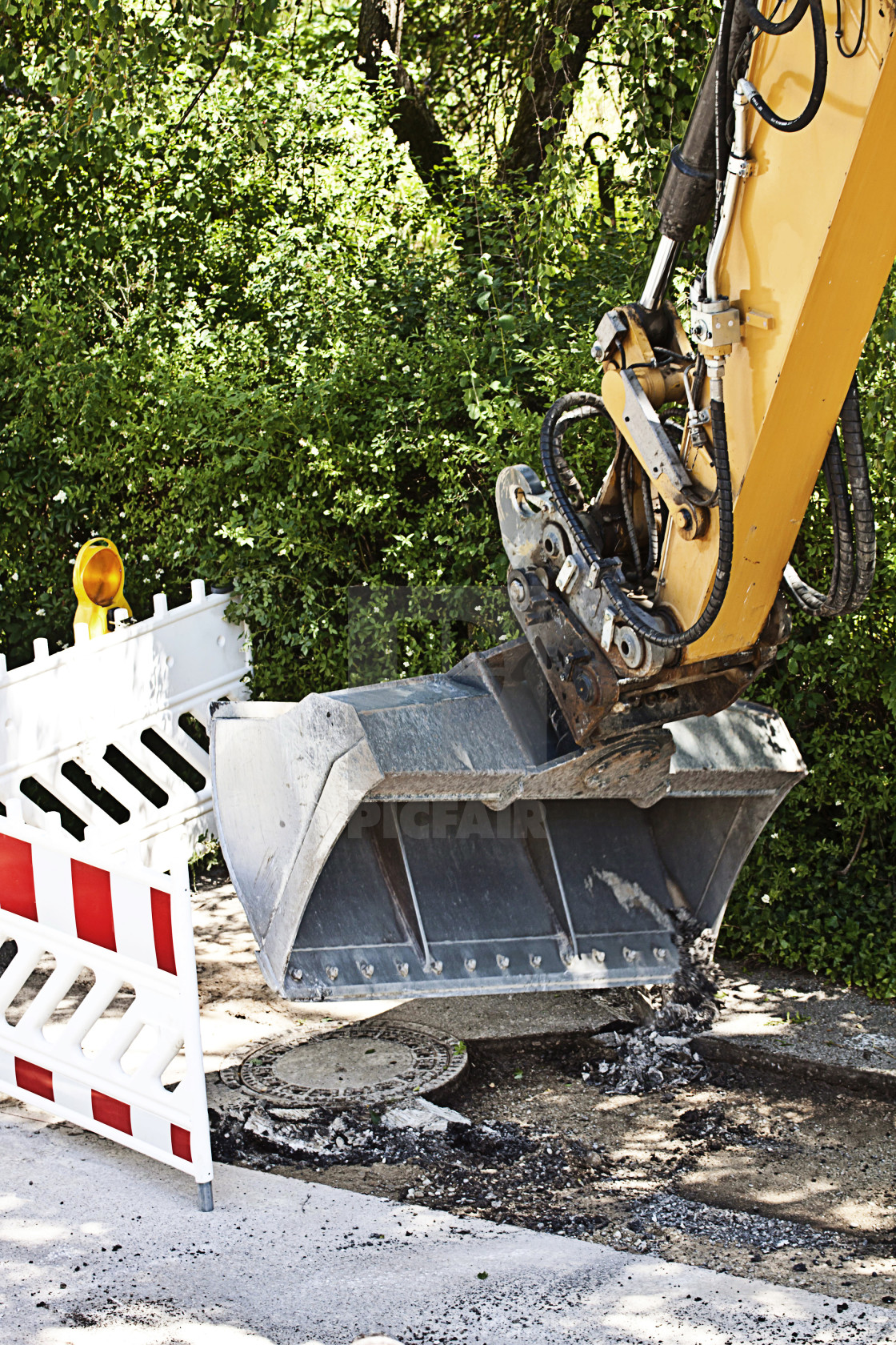 """Road repairing, skid steer loader excavator at work removing old asphalt"" stock image"