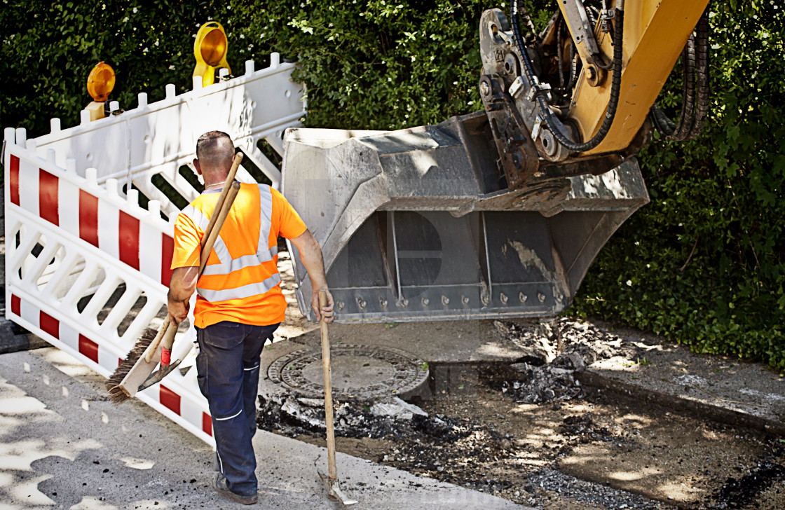 """Road repairing, worker observes a skid steer loader excavator at work ..."" stock image"