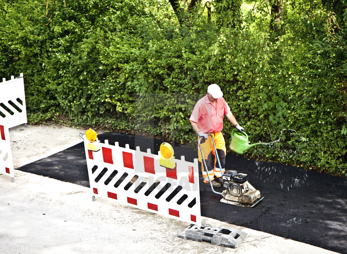 """worker compacts with hand-guided vibratory plates a newly finished asphalt..."" stock image"