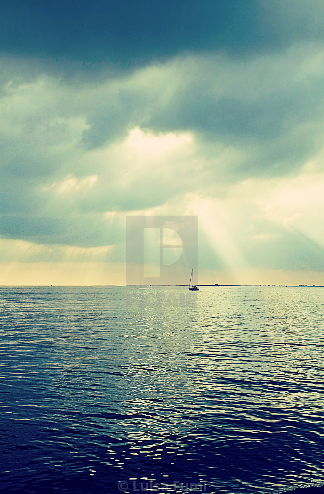 """Quiet after storm, sailboat with sun reflection on calm waters under a..."" stock image"