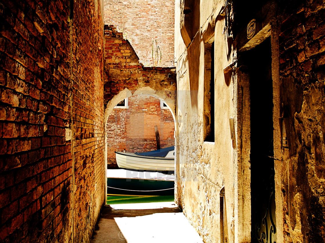 """Venetian underpass with canal and boat"" stock image"