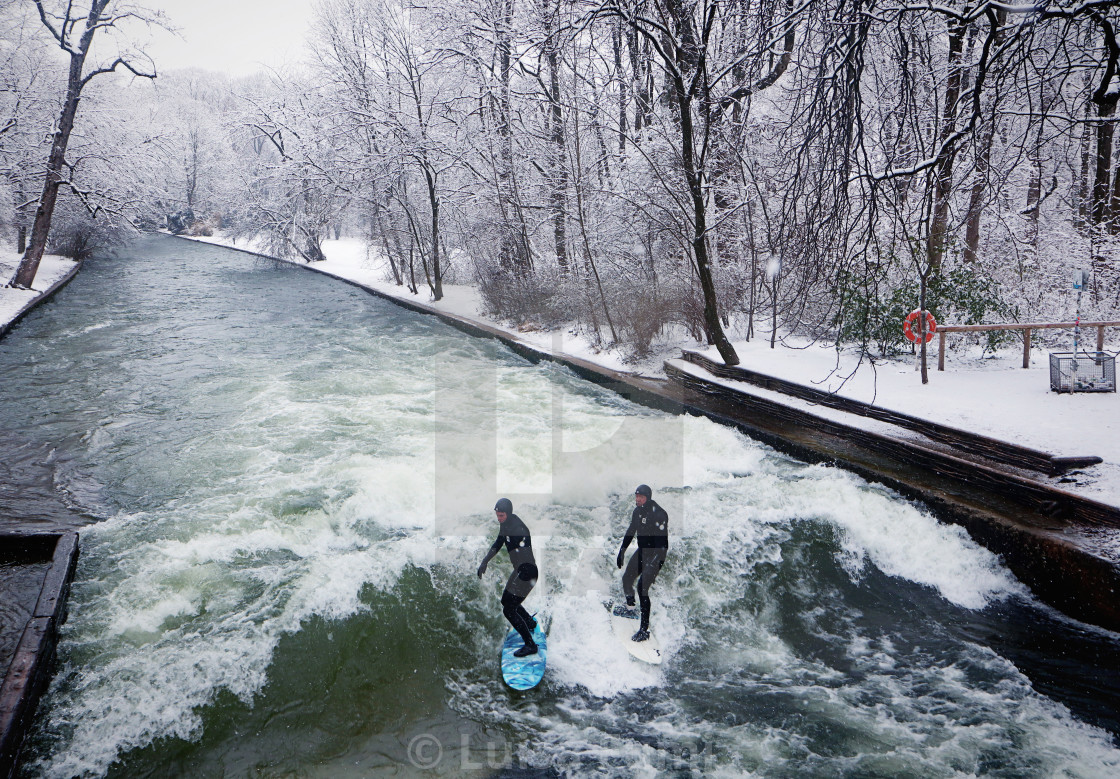 """MUNICH, GERMANY - surfers riding the artificial wave on the Eisbach in winter"" stock image"