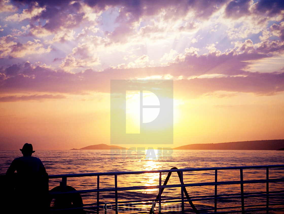 """Man on a ferry looking at sunset"" stock image"