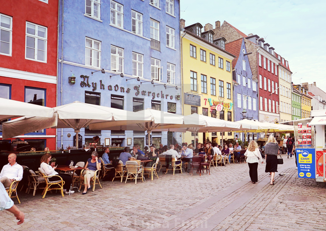 """""""COPENHAGEN, DENMARK - MAY 15, 2018 Panoramic view of Nyhavn harbor waterfront with bars and restaurants, famous touristic landmark and entertainment district of Copenhagen, flanked by colorful antique houses"""" stock image"""