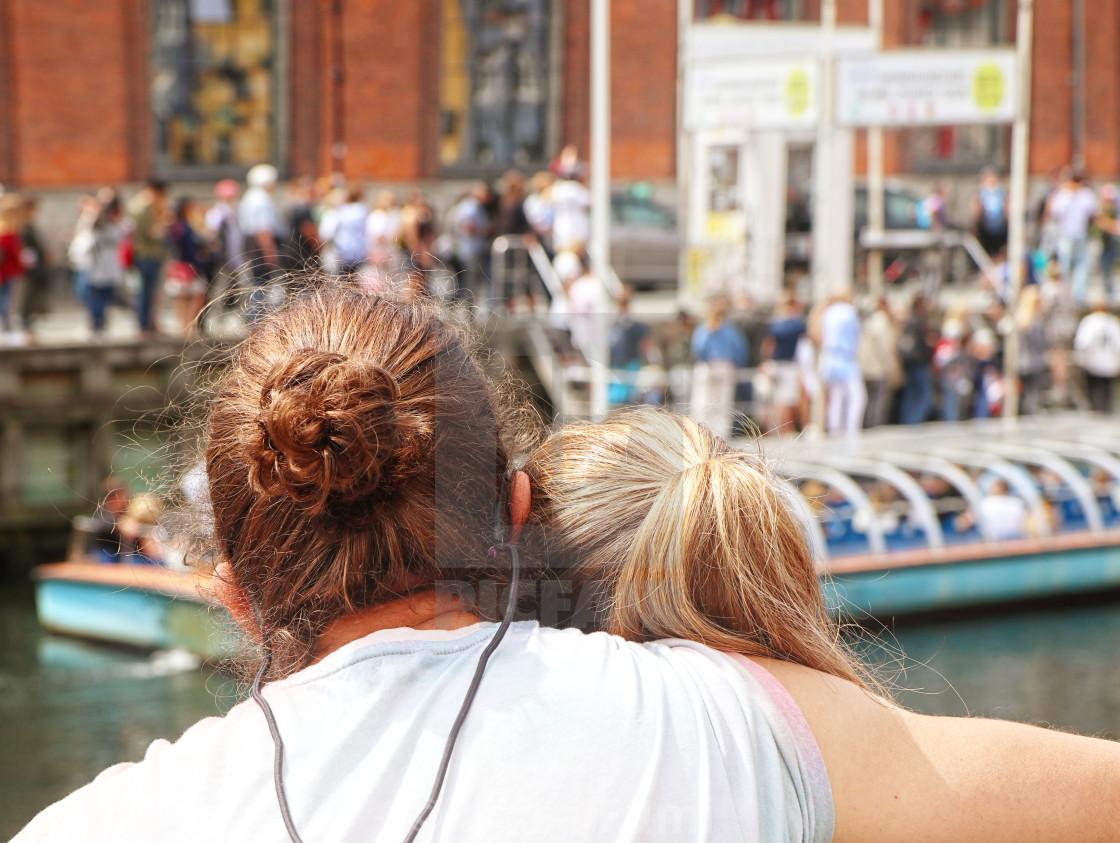 """COPENHAGEN, DENMARK - JUNE 16, 2019 Young couple at Nyhavn harbor, famous..."" stock image"