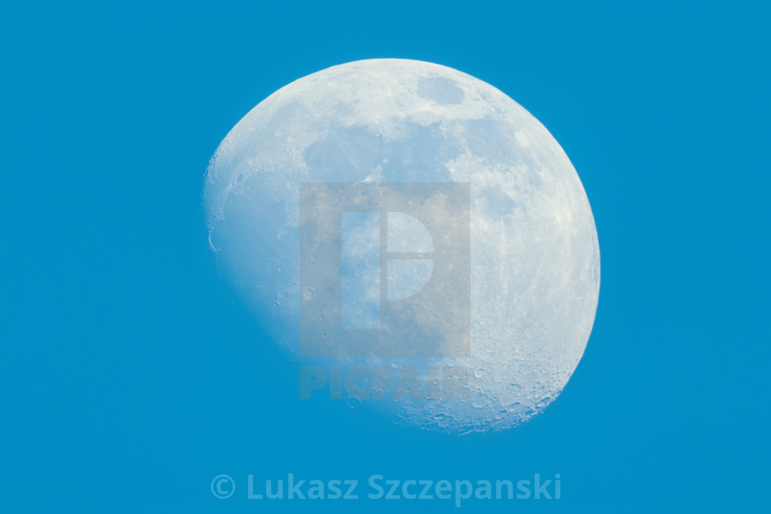 """Moon in Waxing Gibbous phase on the daytime blue sky"" stock image"