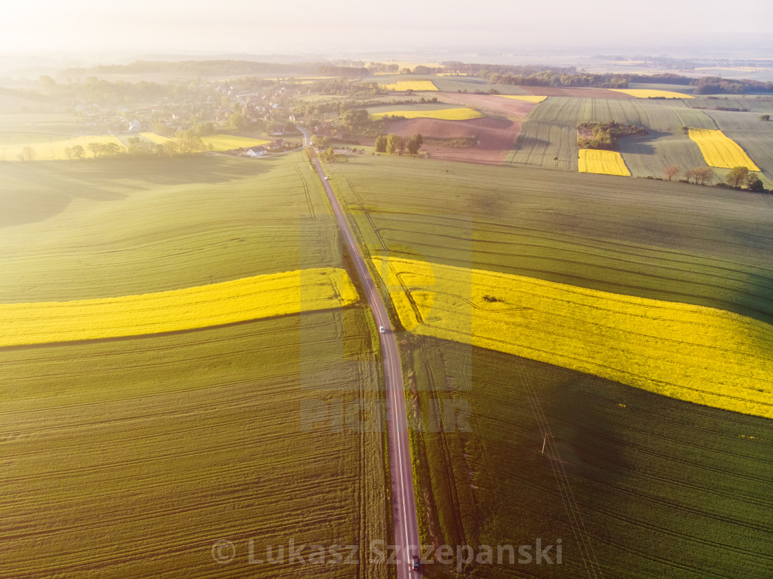 """""""Aerial view of yellow colza and green corn and distant village at sunset"""" stock image"""