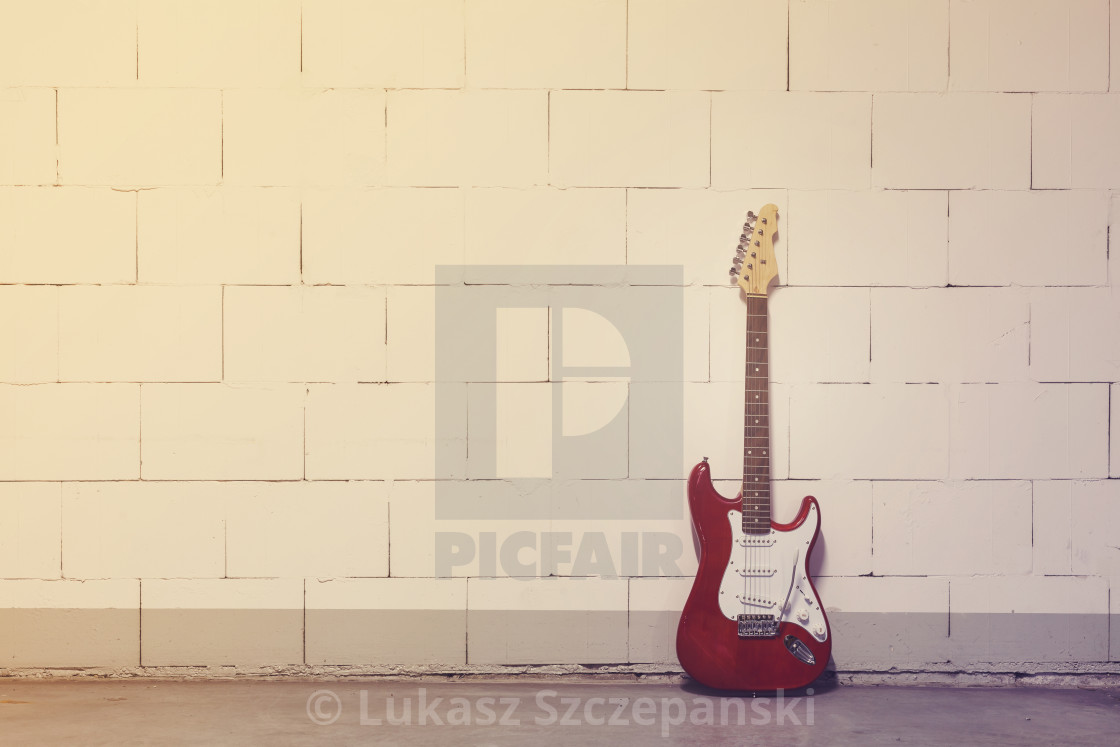 """Red electric guitar stands to the right against white brick wall, yellow magenta toned image"" stock image"