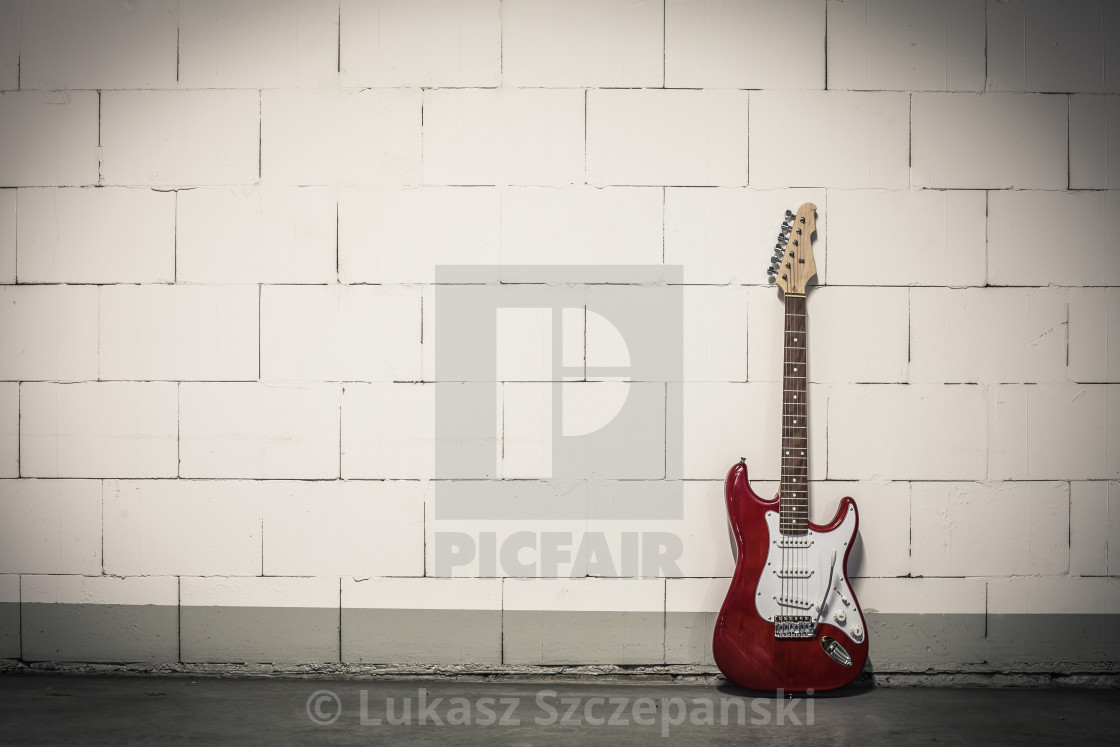 """""""Red electric guitar stands to the right against white brick wall, toned vignette crisp image"""" stock image"""