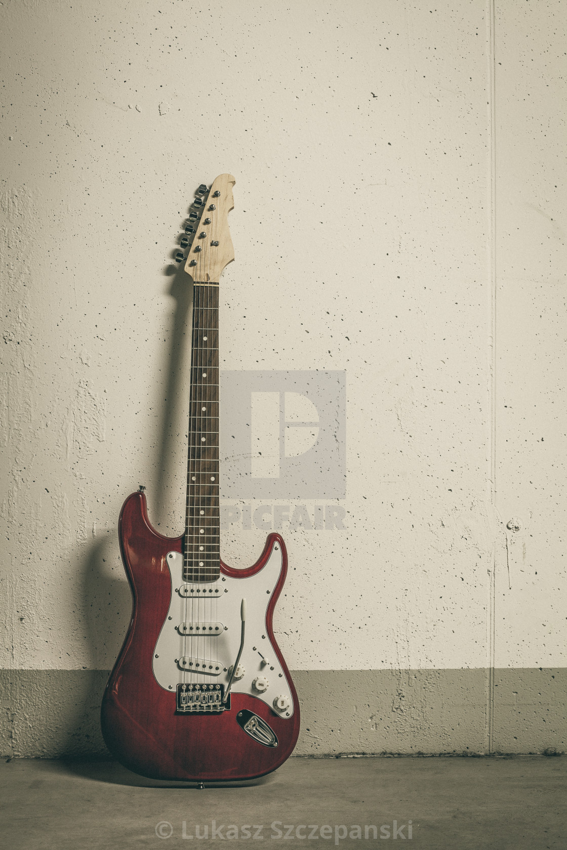 """Red electric guitar standing against white raw wall, toned vignette image"" stock image"