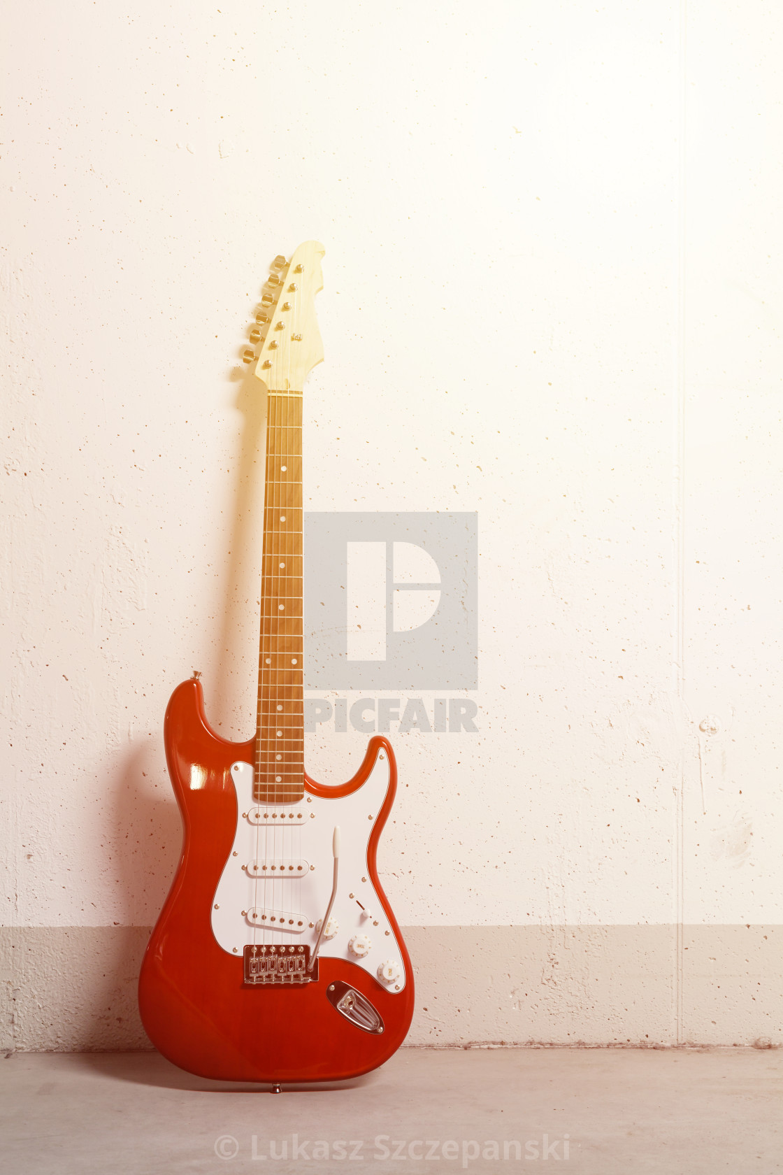 """Red electric guitar standing left against white raw wall with bright yellow sunbeam"" stock image"