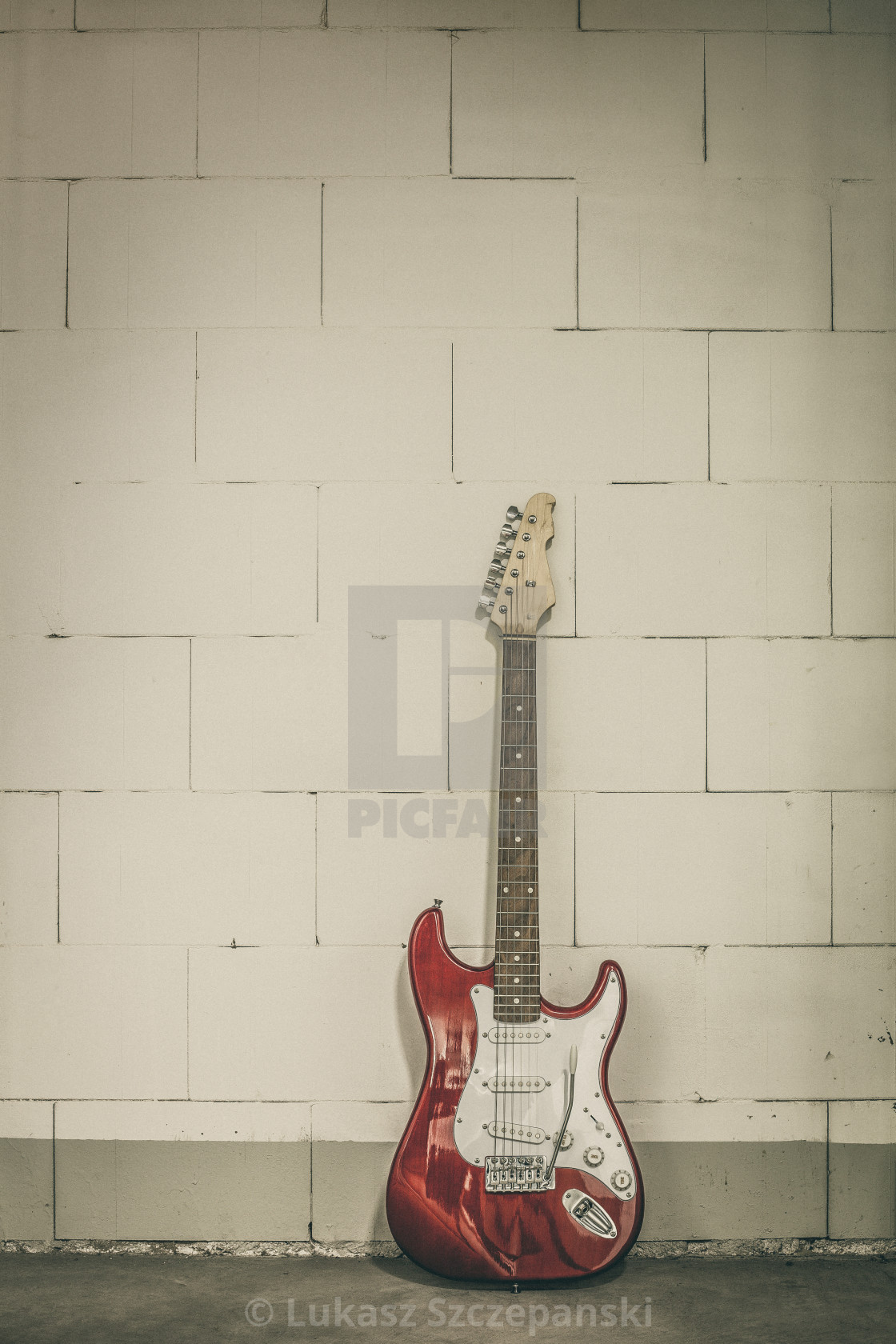 """Red electric guitar stands against white brick wall background, olive toned and dim vignette image"" stock image"