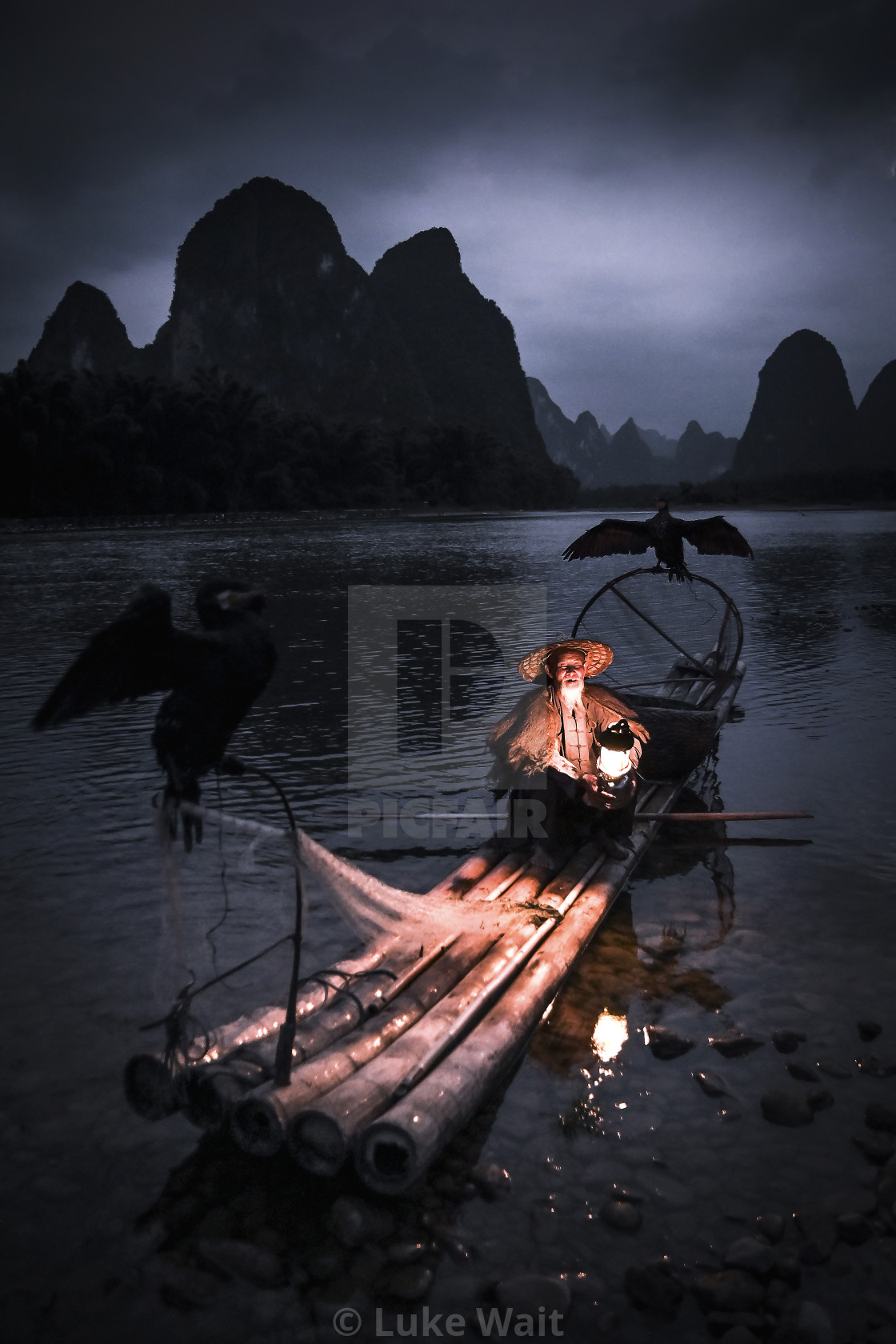 """Cormorant fisherman setting in for the night"" stock image"