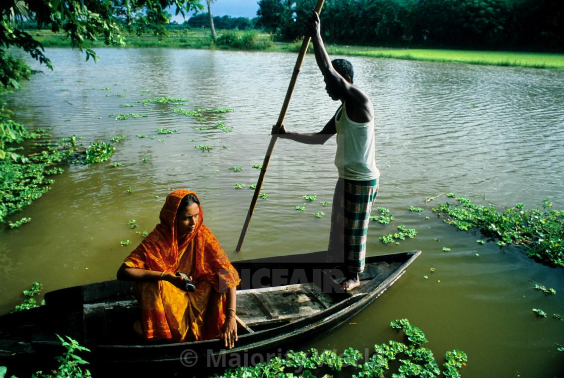 """Fatema Begum and her husband, Badruddin Zaman, cross a flood zone to visit a..."" stock image"