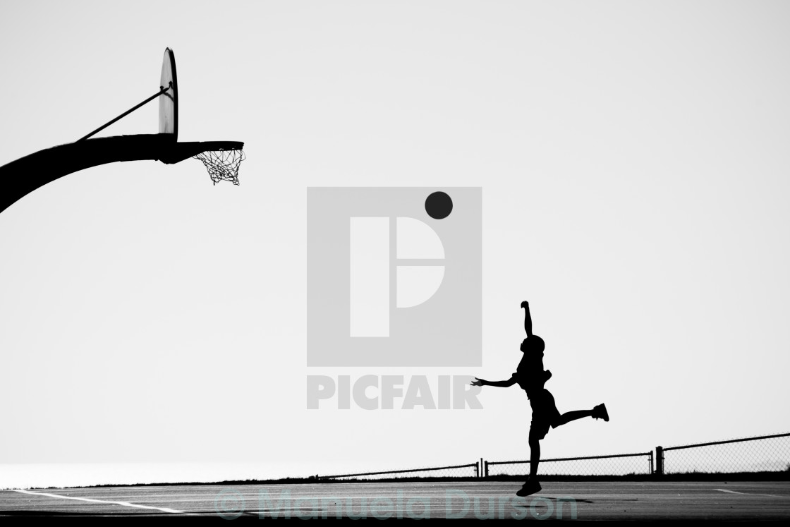 """Silhouette of Boy playing Basketball"" stock image"