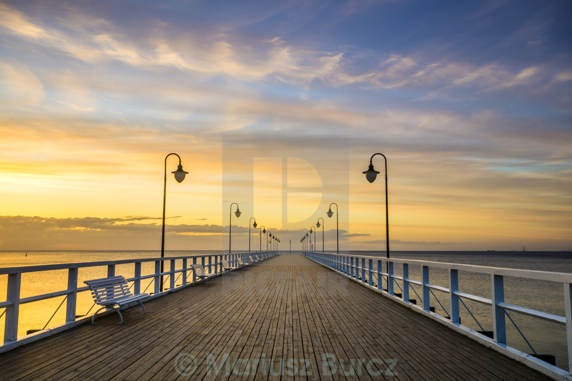 """wooden pier by the sea lit by stylish lamps at night"" stock image"