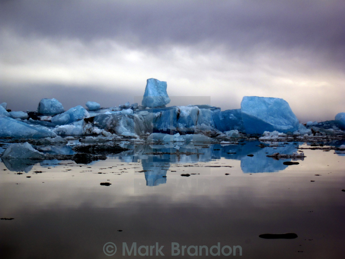 """Blue icebergs under a stormy sky"" stock image"