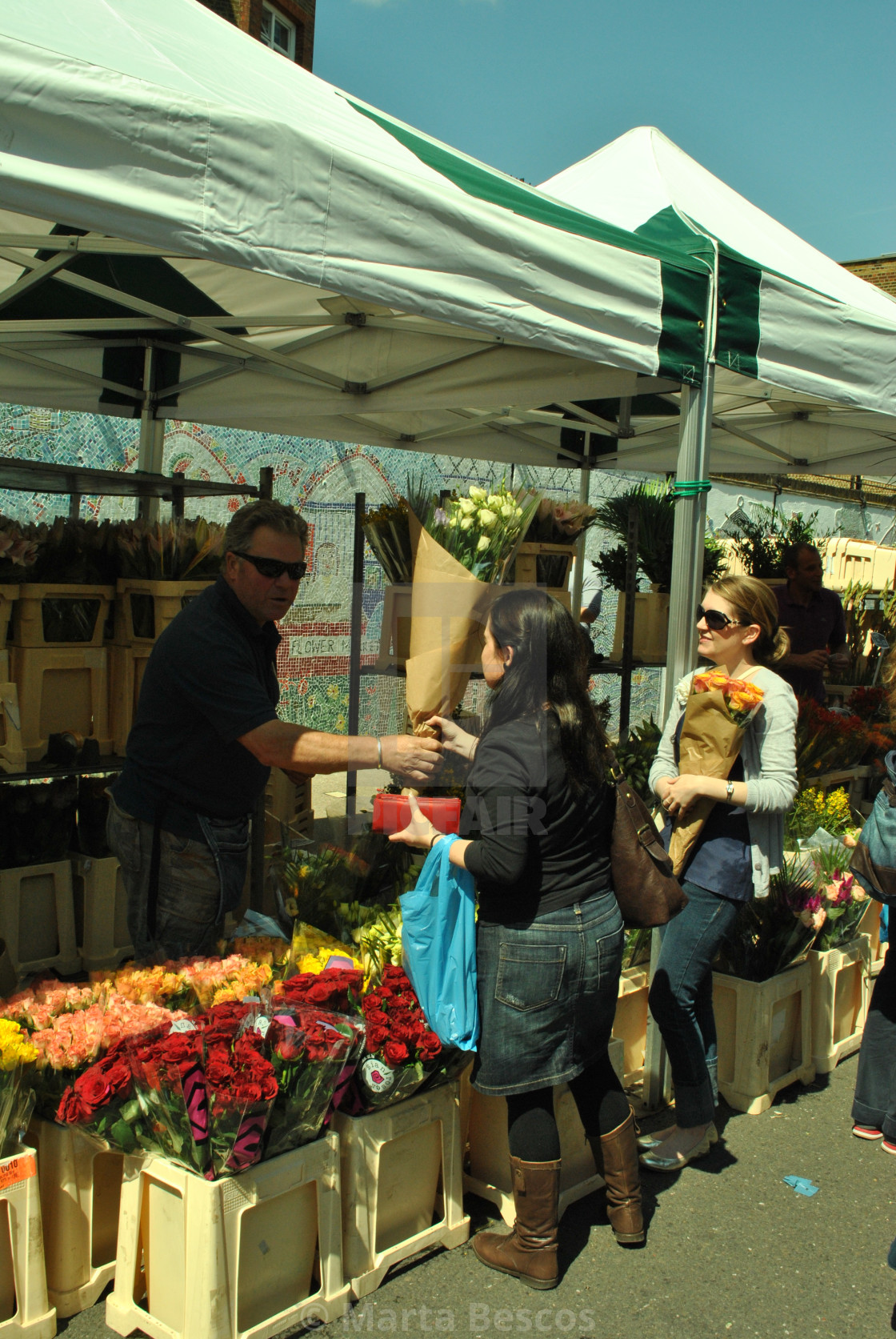 """""""A woman buying flowers at columbia road flower market in east london"""" stock image"""